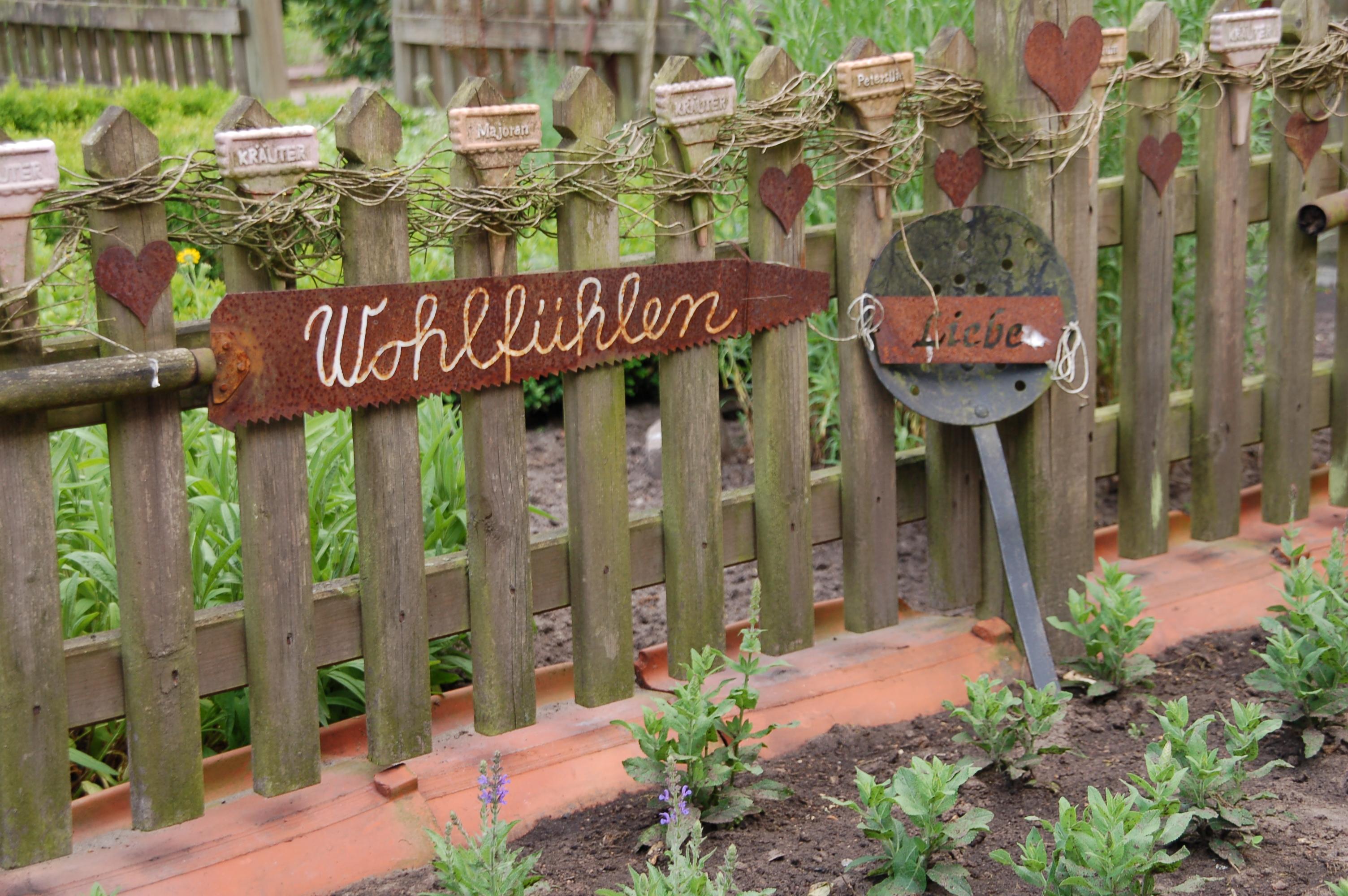 rostiges Sägeblatt mit weißer Schrift, alter Schaumlöffel, rostige Herzen als Gartendeko
