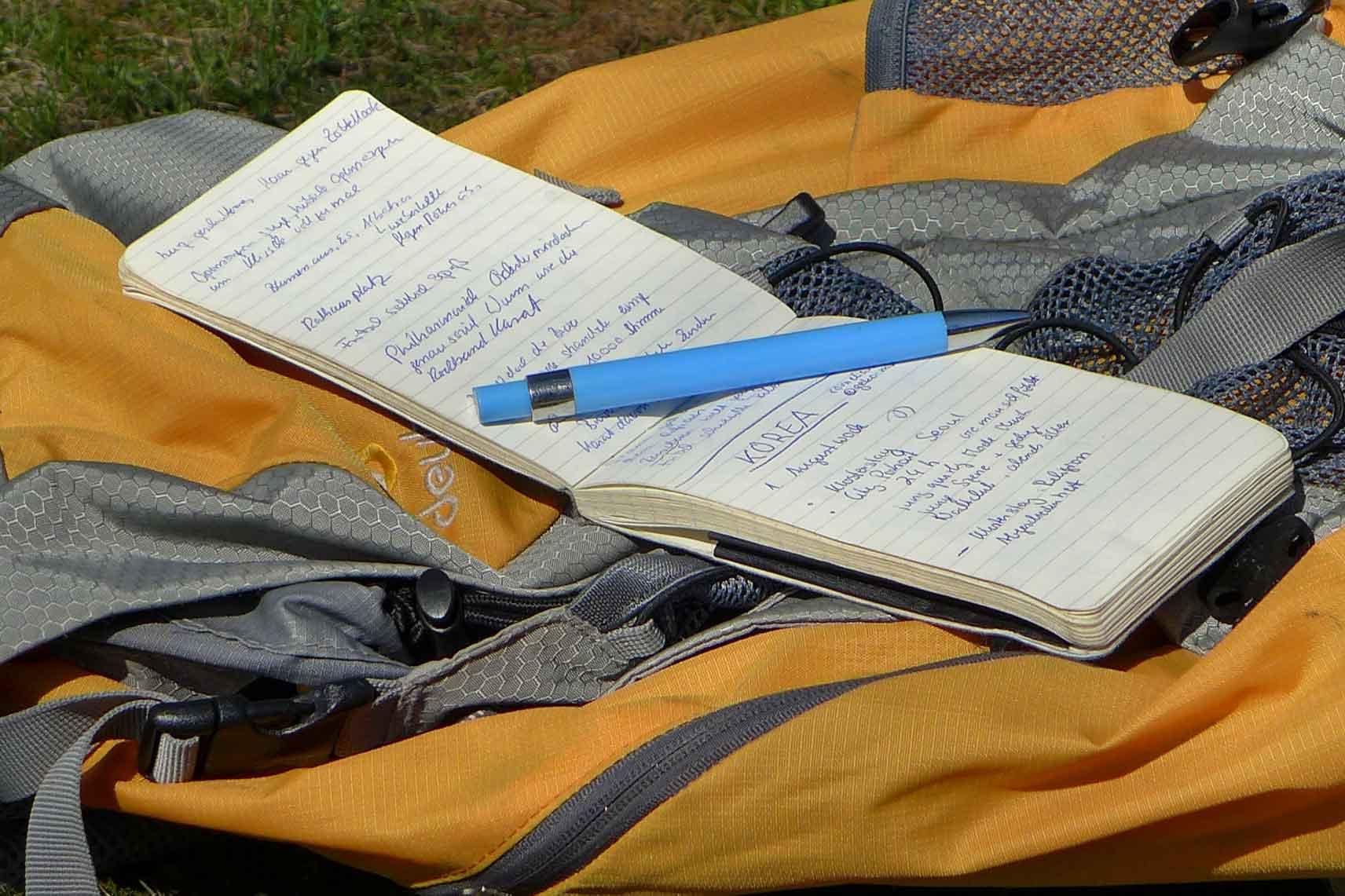 Ein aufgeschlagenes Reporter-Moleskine auf einem Rucksack