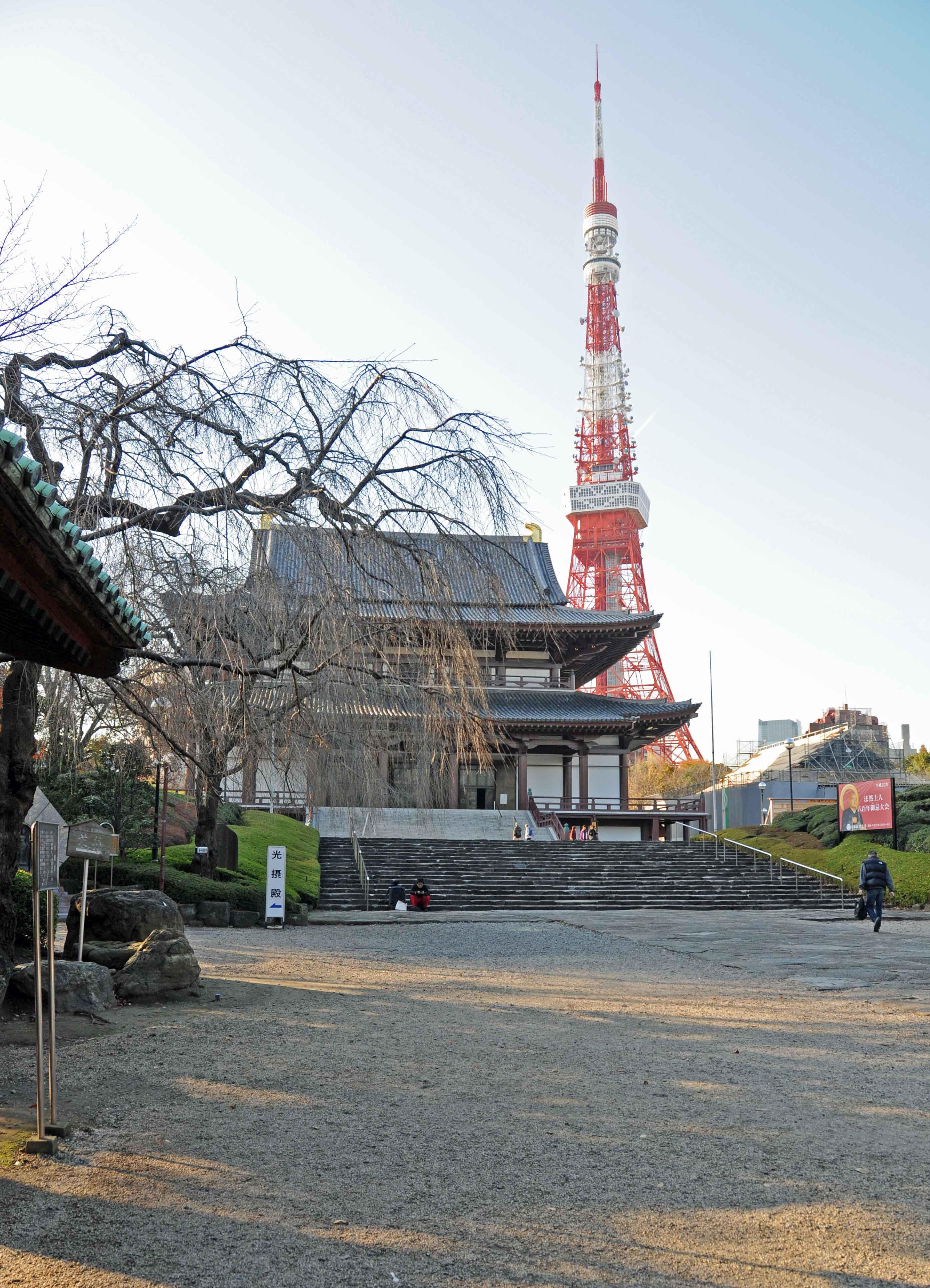 Hinter einem Tempel steht ein rot weiß gestreifter Turm, der dem Eiffelturm nachempfunden ist.