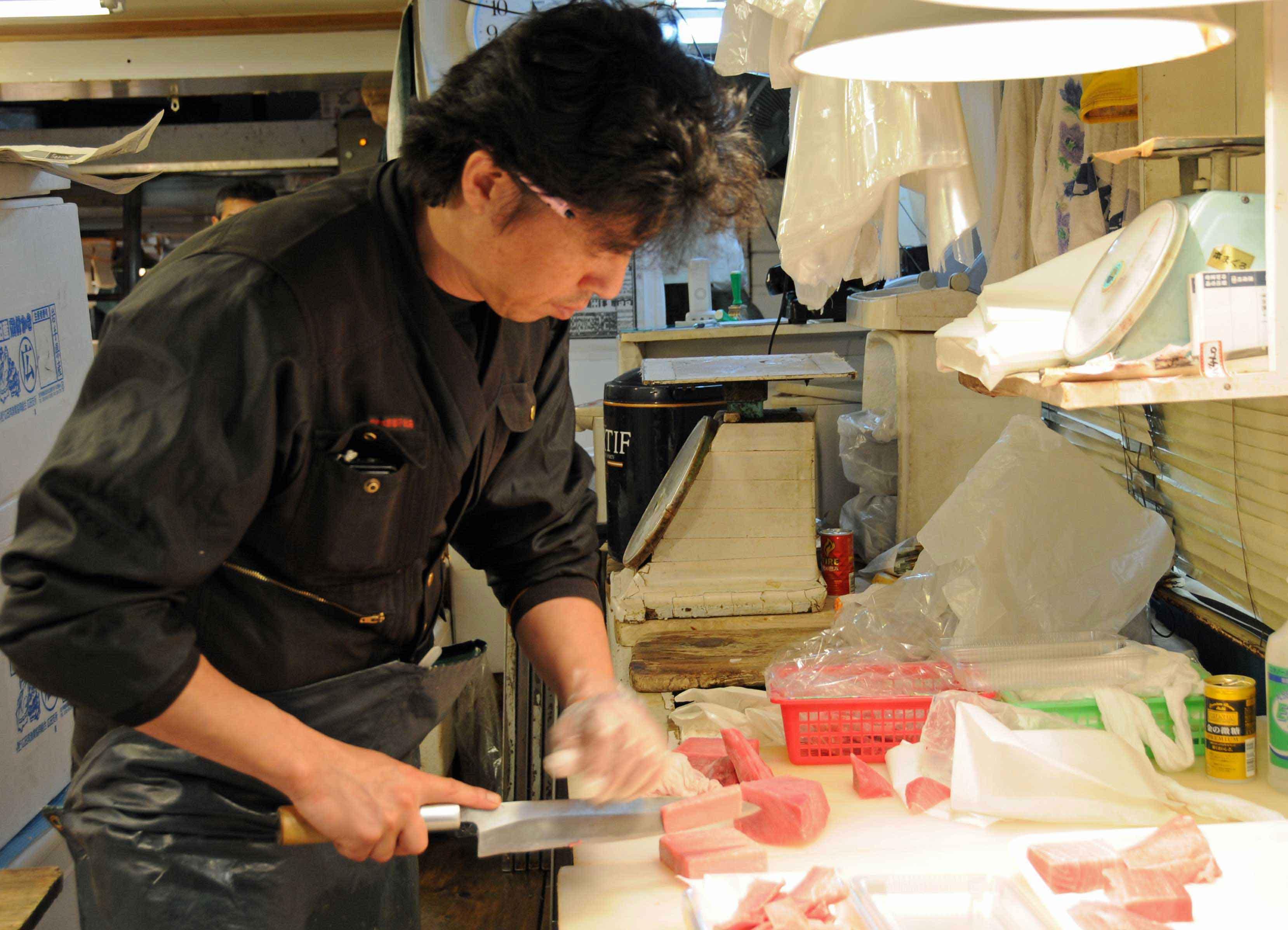Ein Fischhändler schneidet Thunfisch.