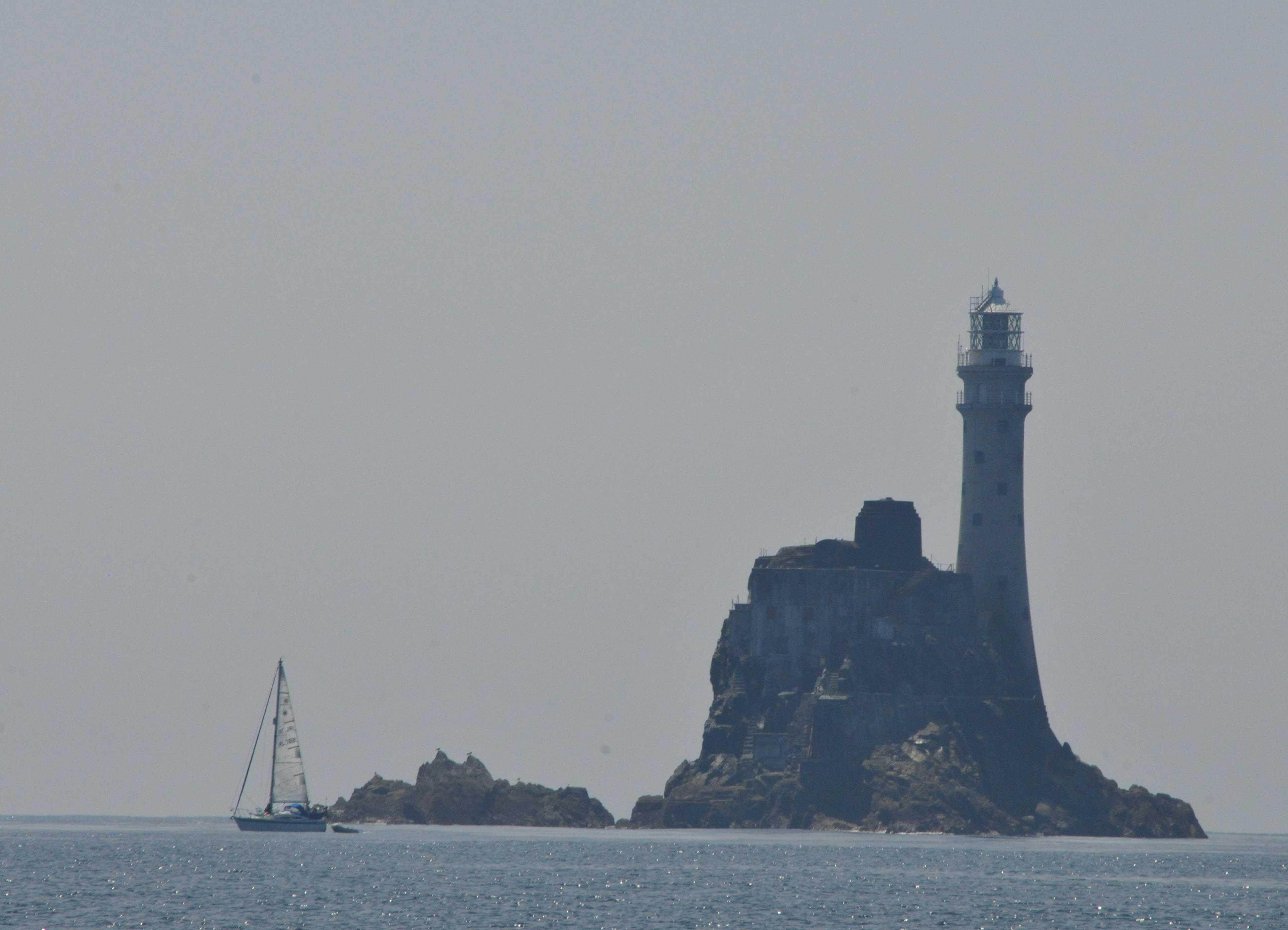Fastnet Rock mit Segelschiff im Dunst.