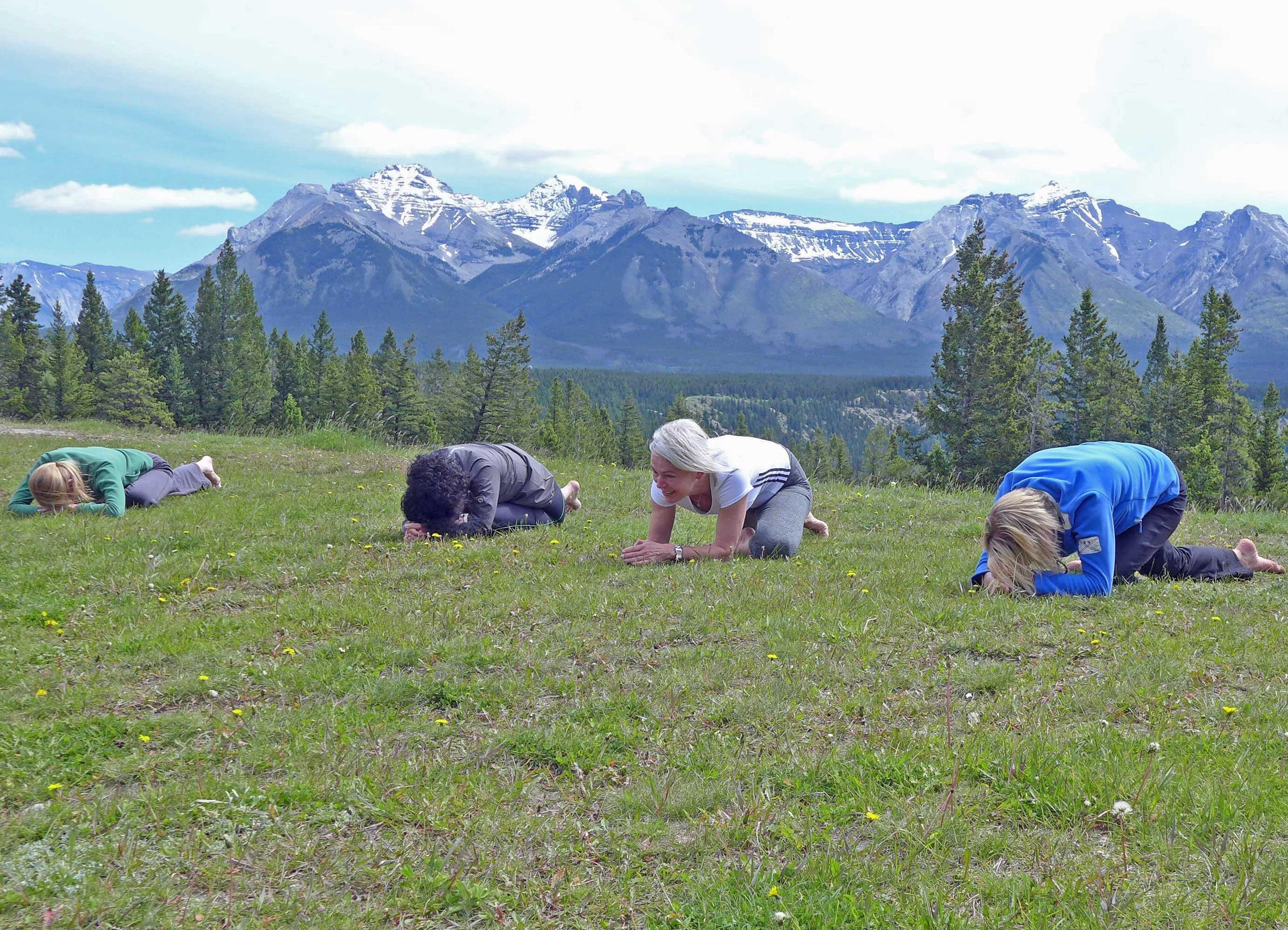 Gruppe macht Yoga vor Bergkulisse