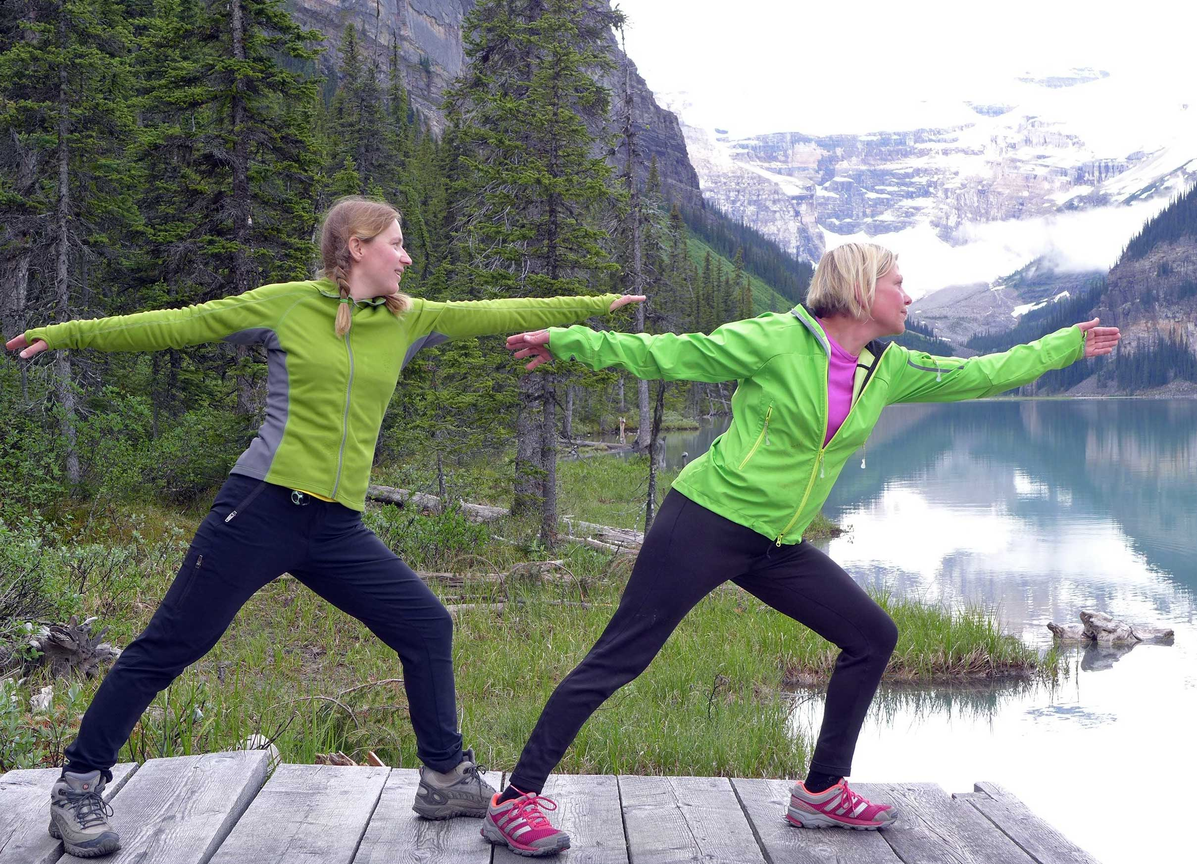 Zwei Frauen in grüner Sportkleidung machen eine Yogaübung.