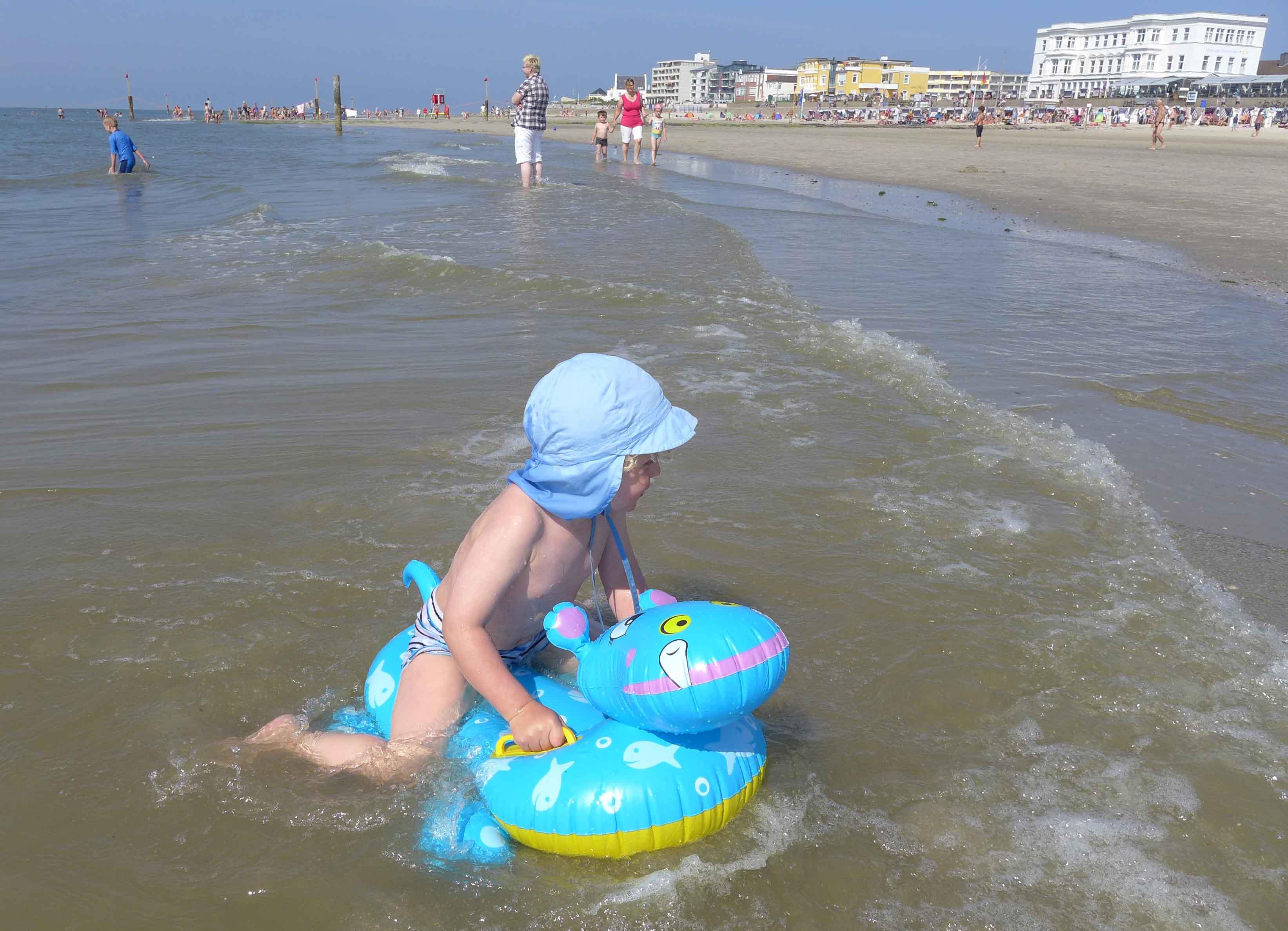 Kleinkind auf einem Schwimmtier  in der Nordsee.