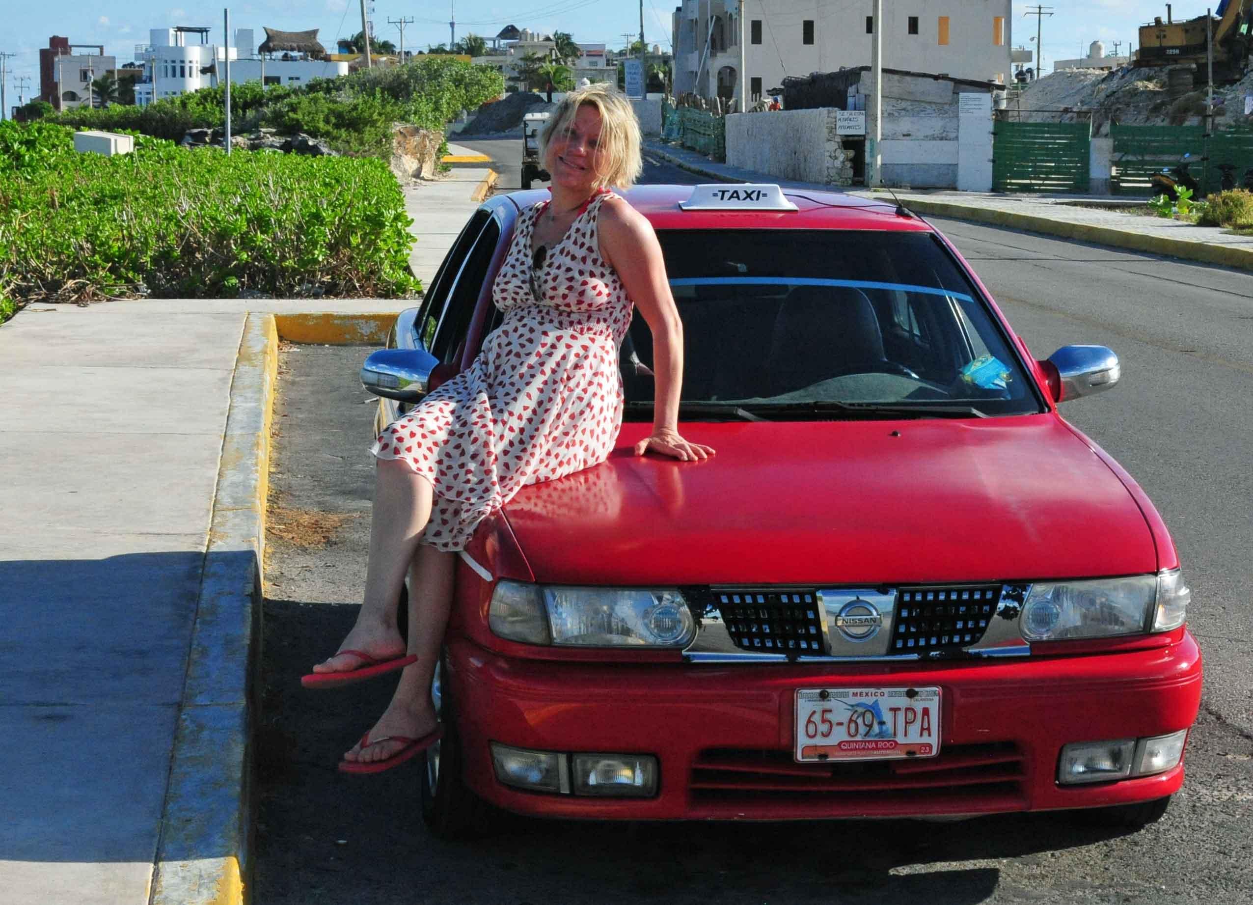 Silke posiert auf der Motorhaube eines roten taxis.