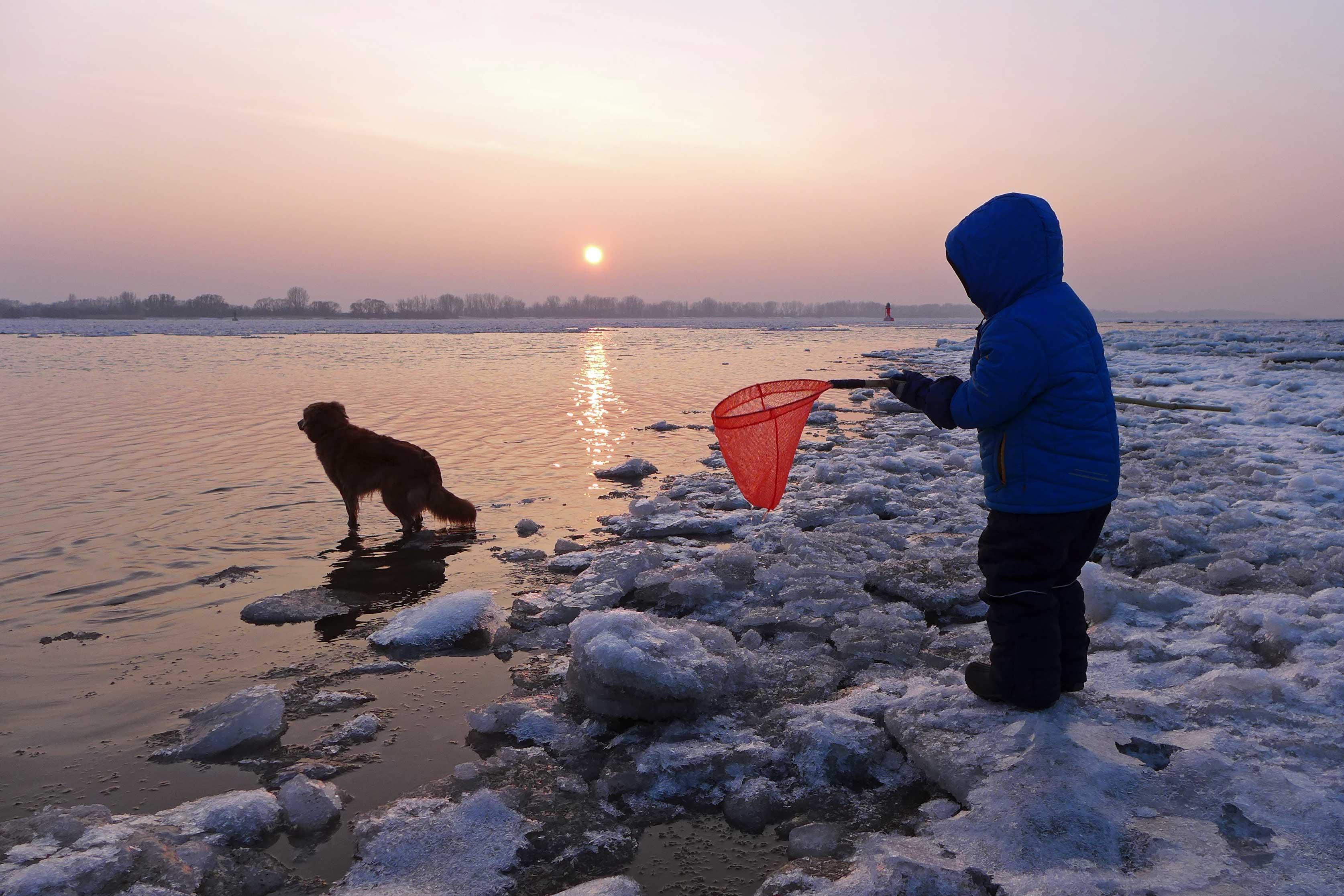 Kind und Hund bei Sonnenuntergang am verschneiten Elbstrand