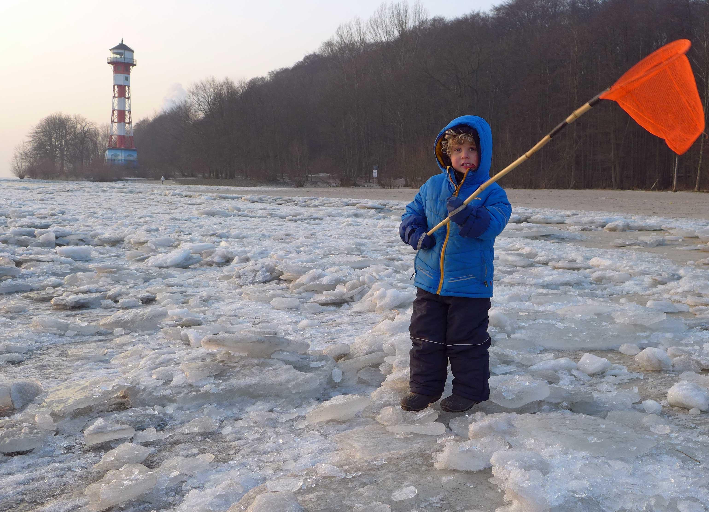 Eis und Schnee am Elbstrand. Kleinkind mit Kescher. Im Hintergrund der Wittenbergener Leuchtturm.