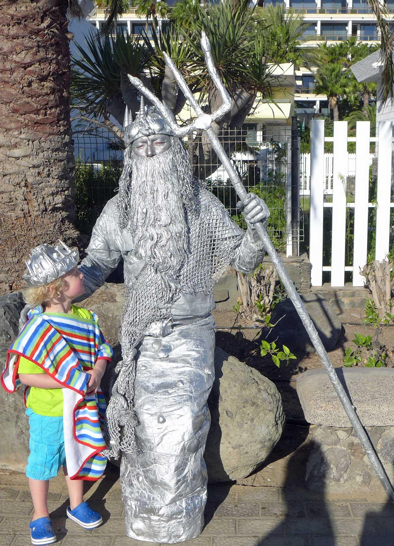 Kleiner Junge neben einem als  Neptun verkleideten Mann