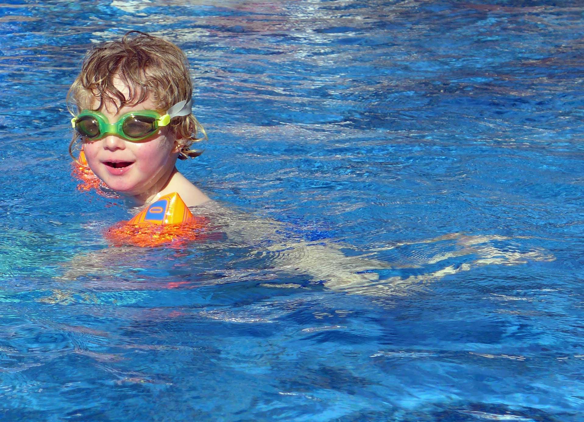 Kleinkind schwimmt im Pool.