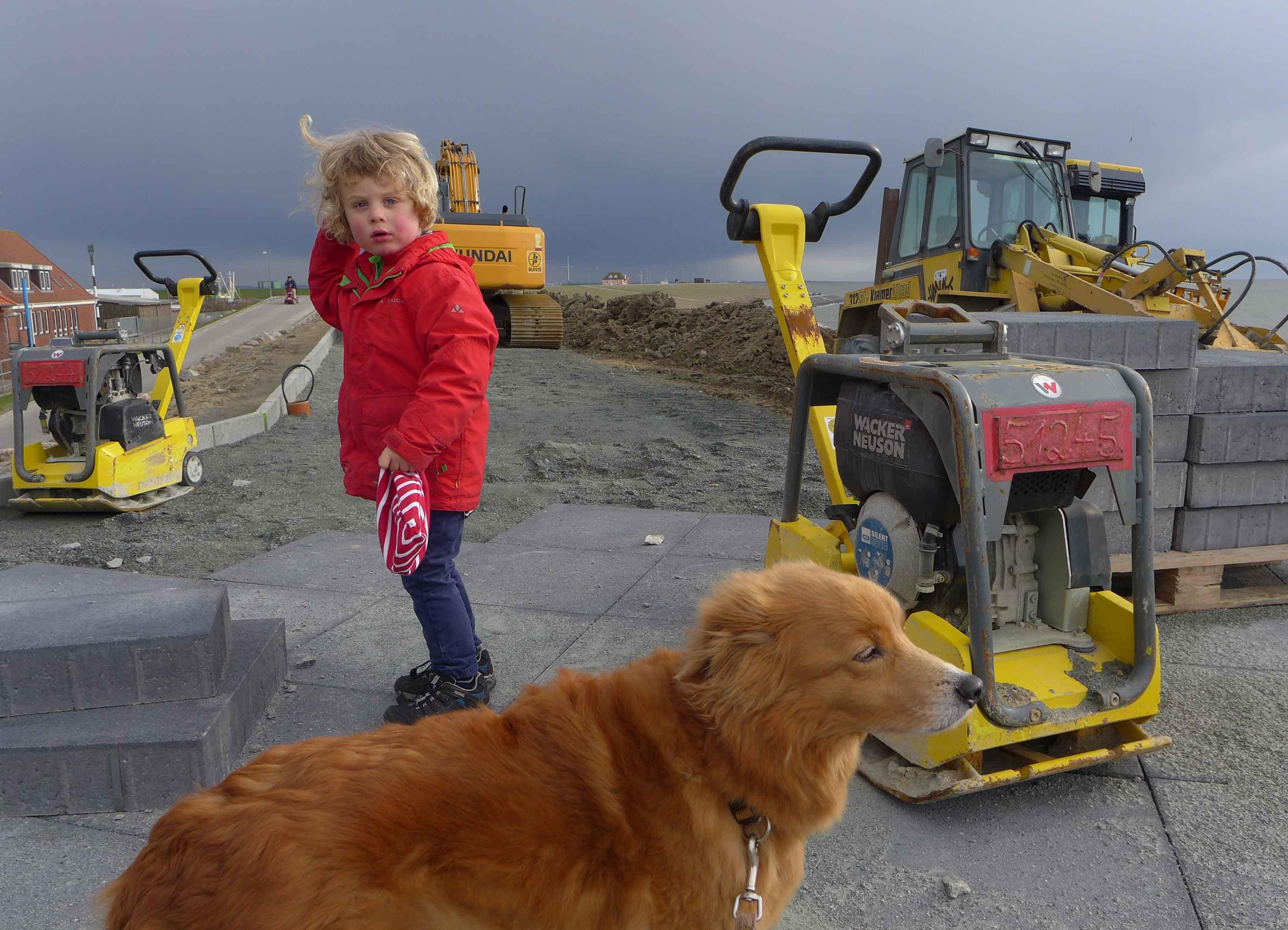 Kind und Hund vor Baumaschinen