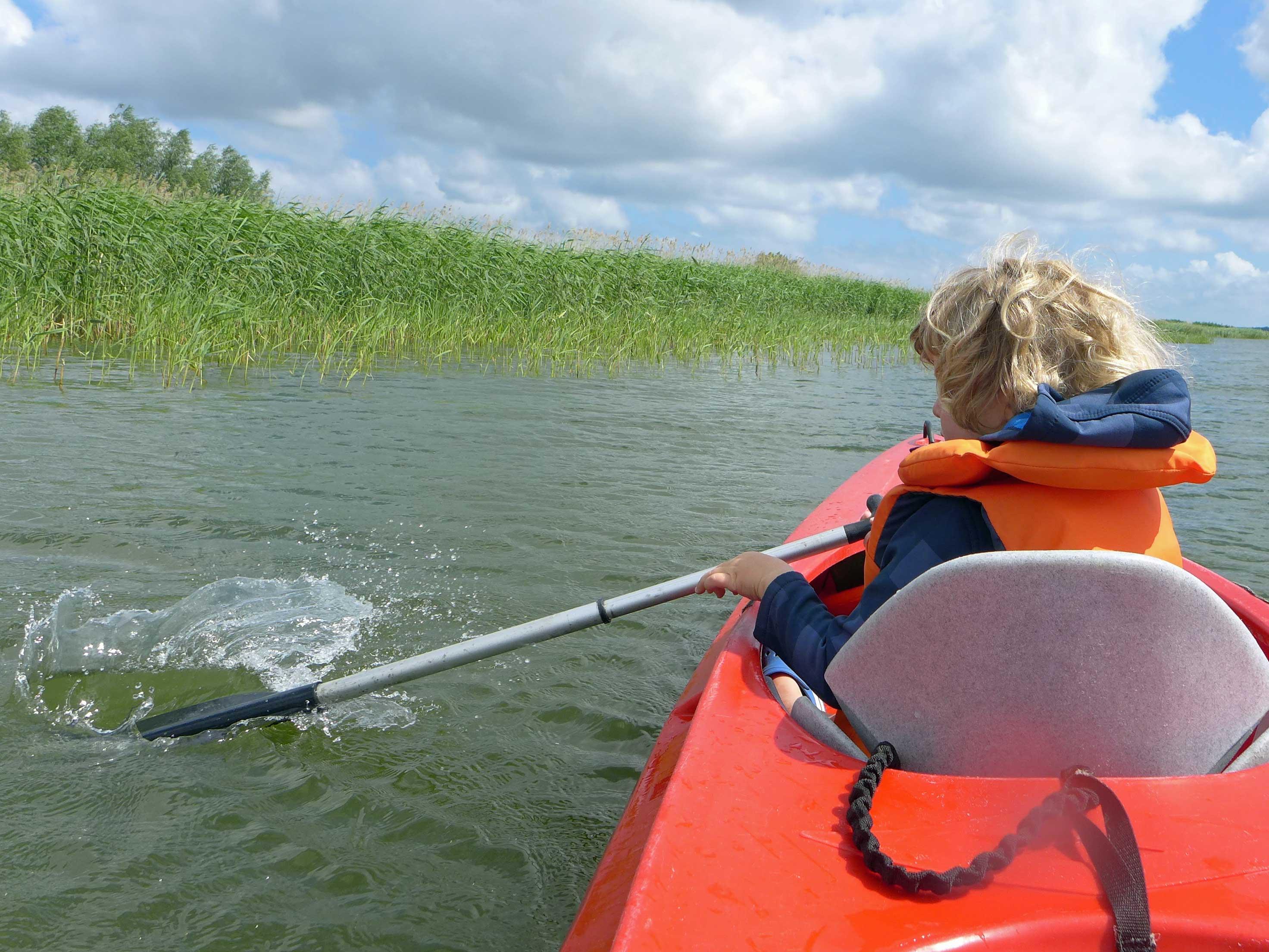 Ein Kleinkind paddelt im Kajak auf dem Usedomer Achterwasser,  Familienurlaub Usedom, Tipps Familienreise, Aktivurlaub mit der Familie, Usedom-Urlaub, Reiseblog. Reisefeder