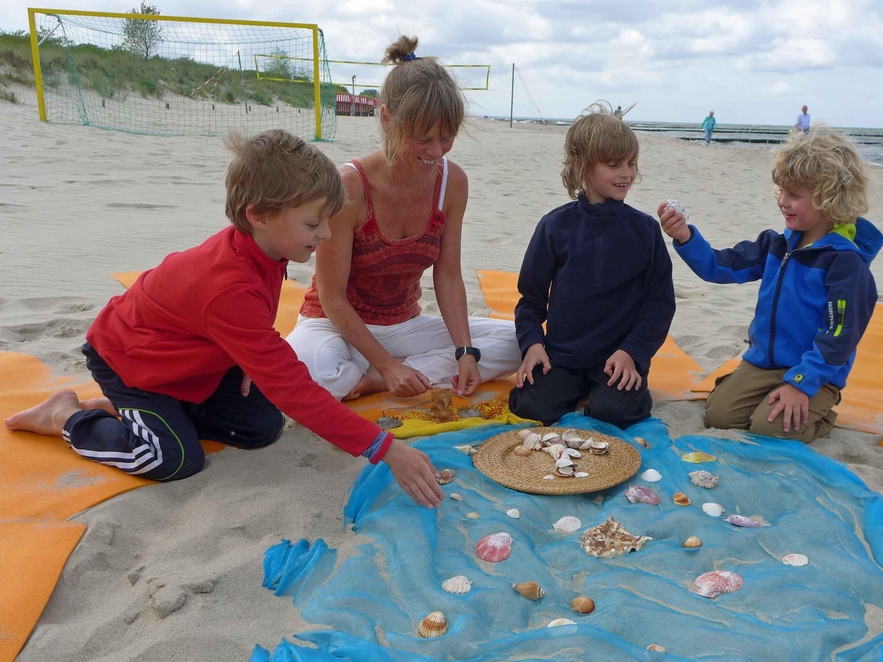 Drei kleine Kinder mit einer Yoga-Lehrerin am Strand von Koserow Familienurlaub Usedom, Tipps Familienreise, Aktivurlaub mit der Familie, Usedom-Urlaub, Reiseblog. Reisefeder