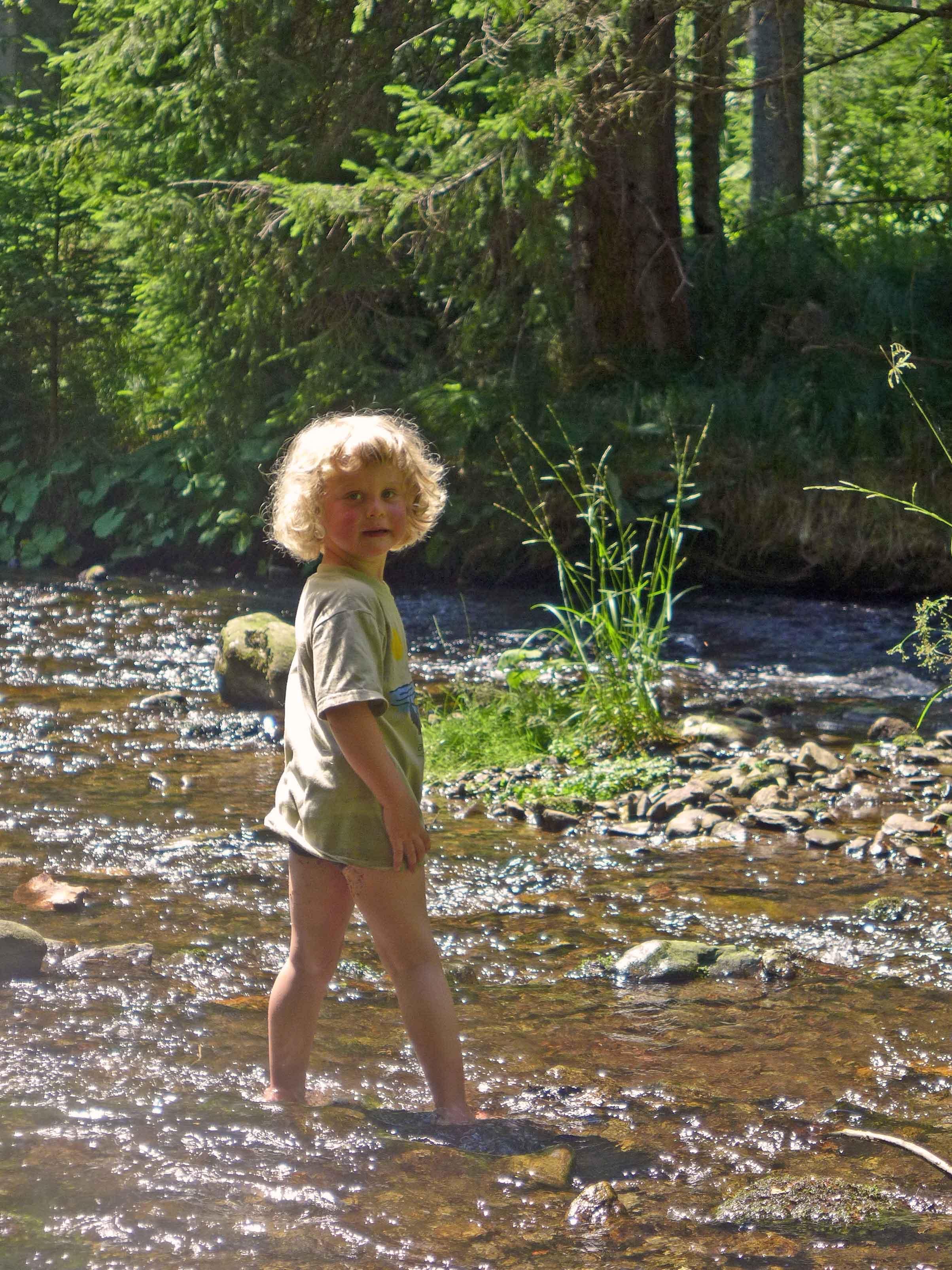 Blondschopf spaziert durch einen Bach