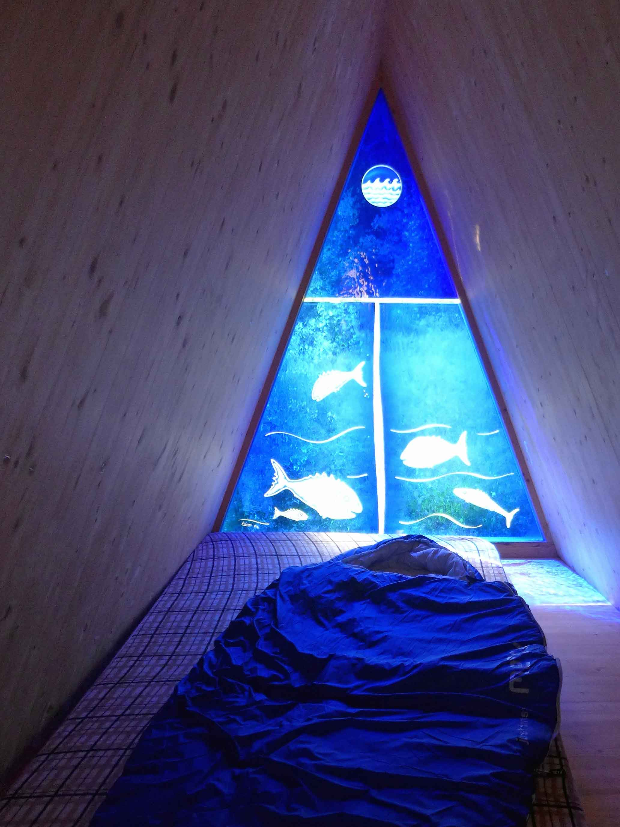 Ein blaues, dreieckiges Fenster mit Fischen