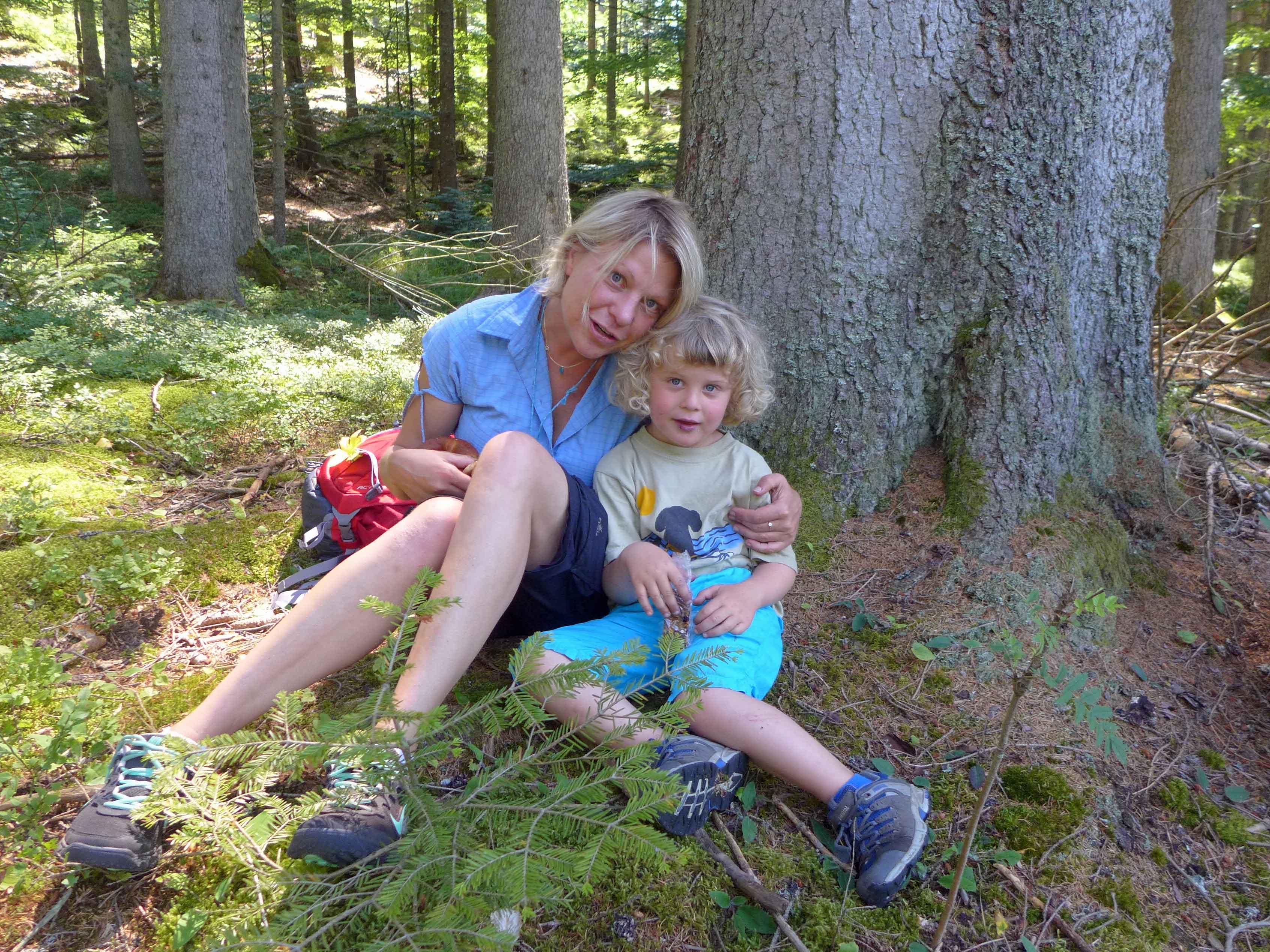 Silke und Frederik rasten im Bayerischen Wald gegen einen Baumstamm gelehnt