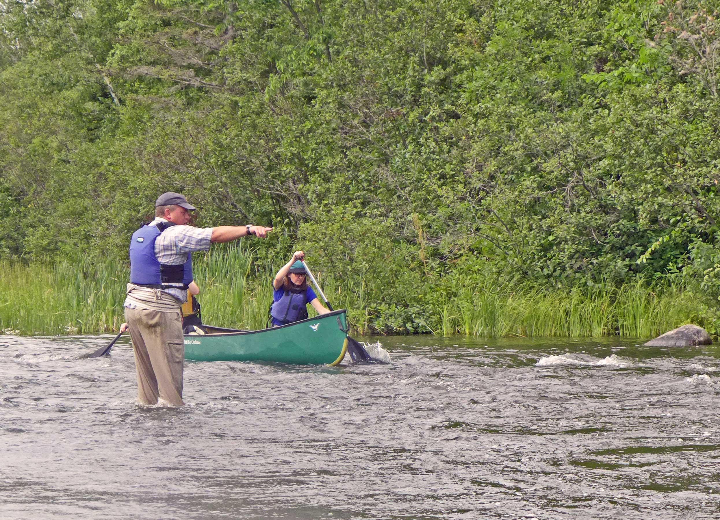 Cameron White steht bis zu den Knien im Pinawa Channel und gibt Paddlern Tipps