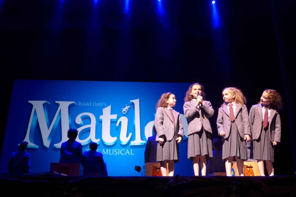 Drei Darstellerinnen in Schuluniform im Musical Matilda