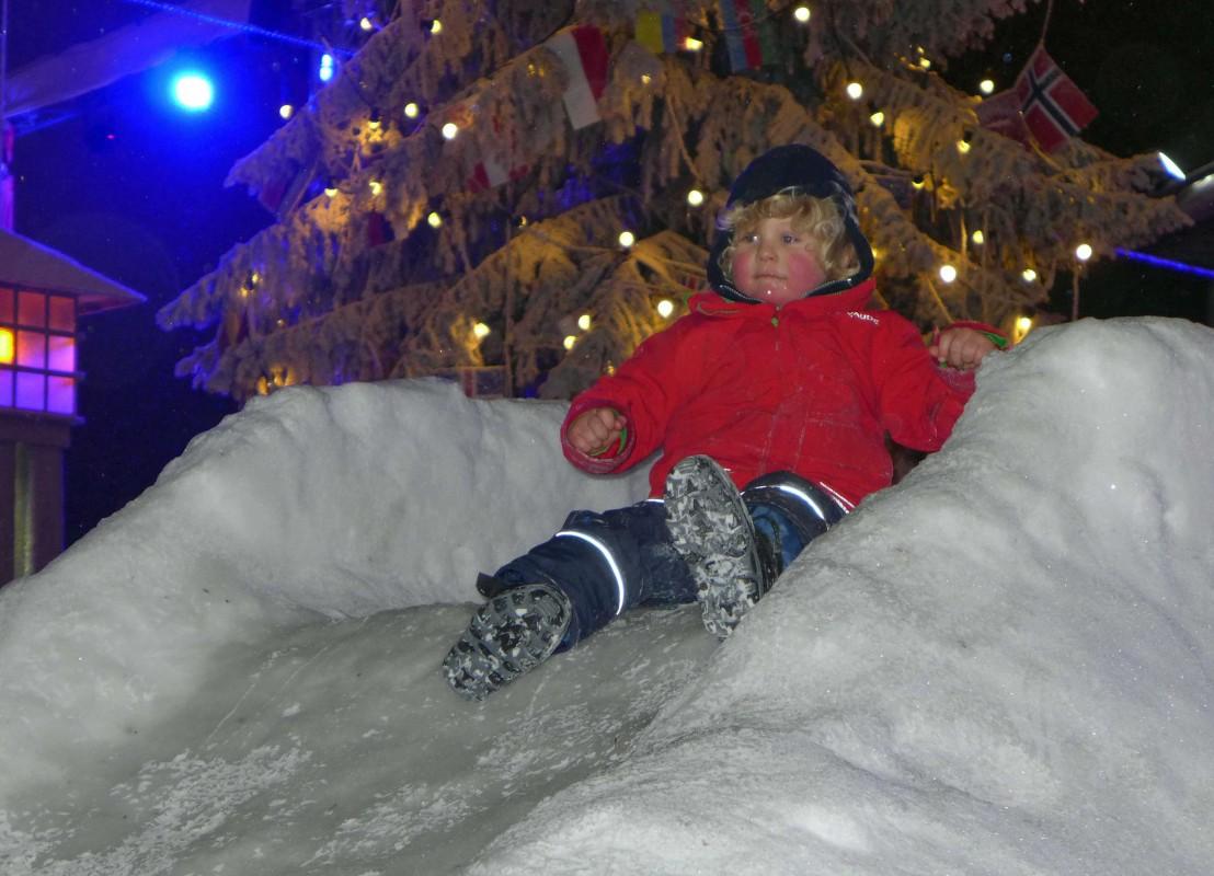 Kind rutscht auf einem Schneeberg hinunter