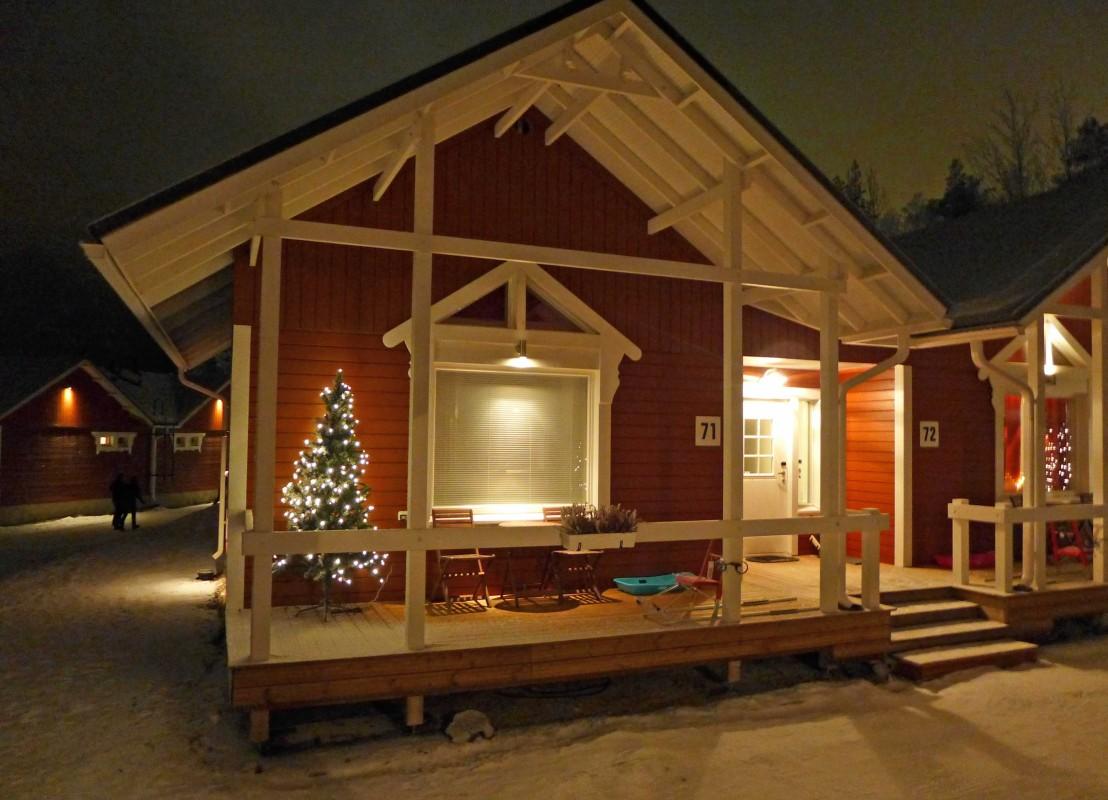 Rotes Ferienhaus mit Weihnachtsbaum auf der Terrasse in Rovaniemi