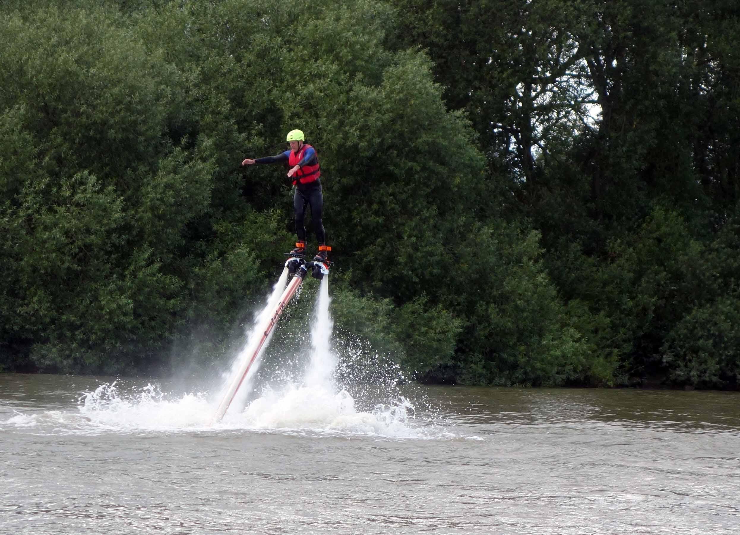 Eine Person wird mit dem Jetovator einige Meter in die Höhe geschleudert, etwa wie reiten auf zwei Wasserfontänen