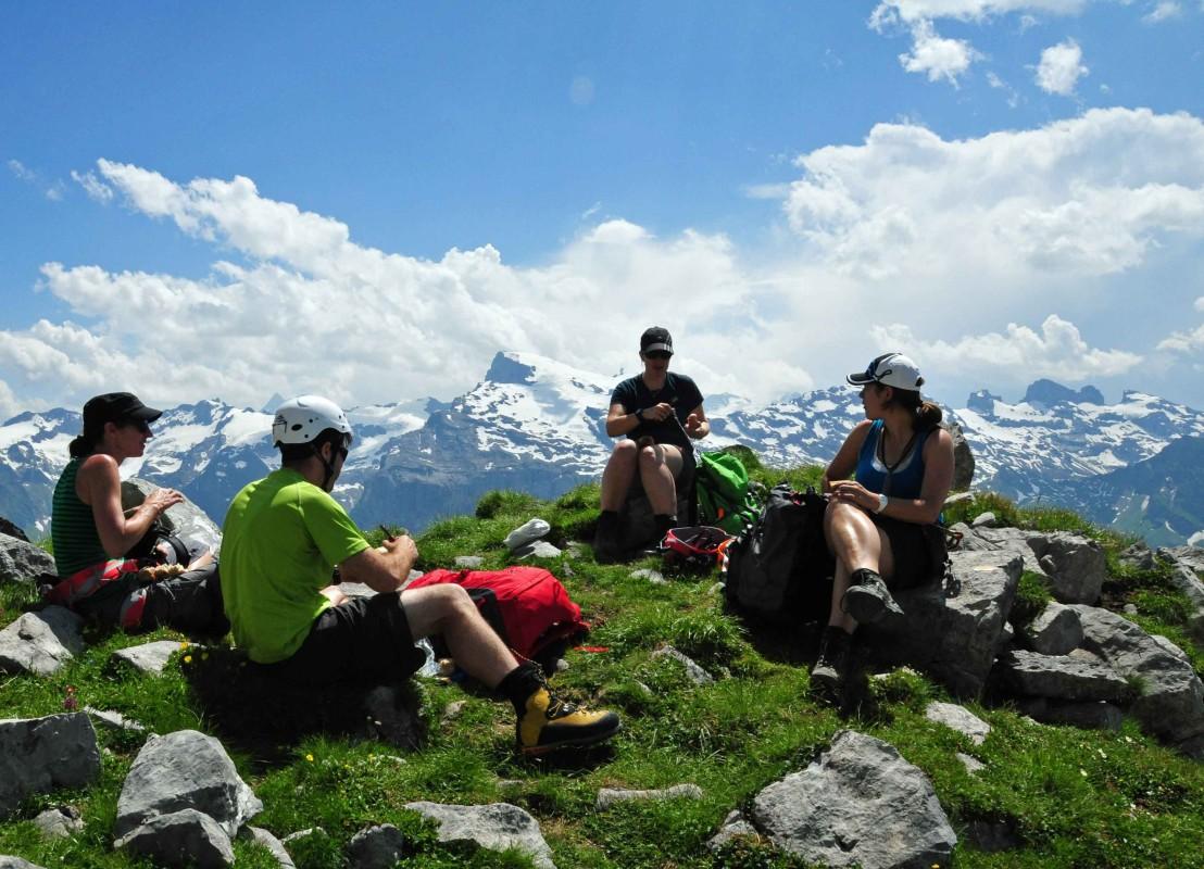 Wanderer machen ein Picknick auf dem Berg mit Gipfelpanorama