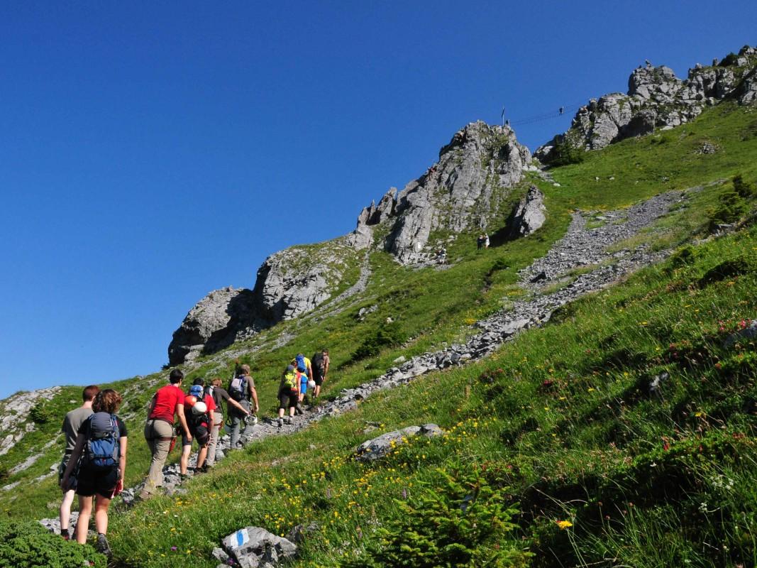 Wandergruppe marschiert einen steinigen Pfad zum Klettersteig Engelberg
