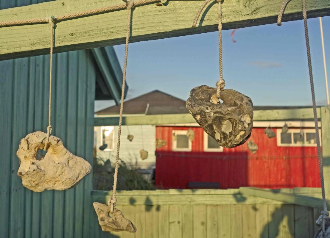 Hühnergötter hängen vor einem Strandhaus. So heißen Steine mit natürlichen Löchern. Sie sollen Glück bringen, dem Finder und dem Beschenkten