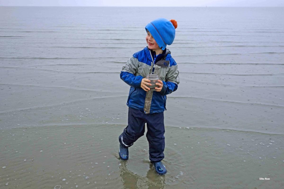 Klatschnasses Kind stapft lächelnd durchs Watt