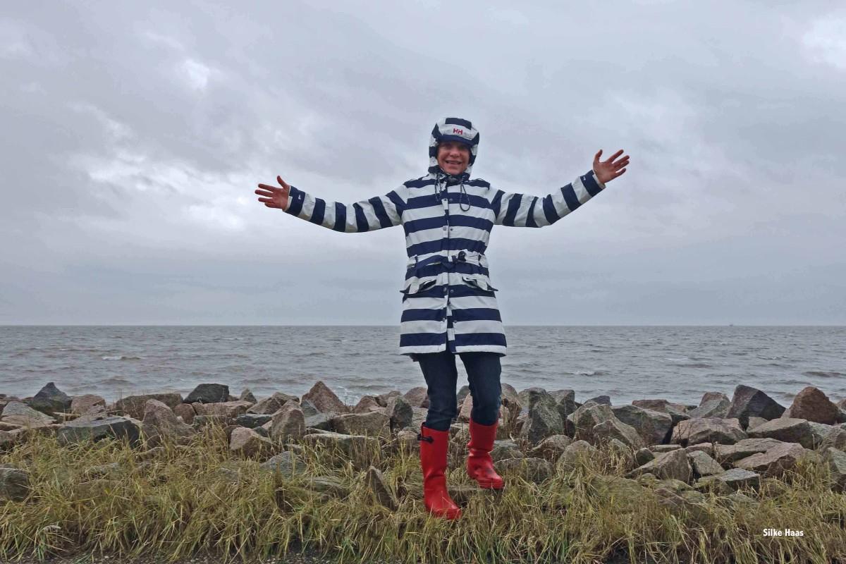 Frau mit erhobenen Armen und im Regenmantel und Gummistiefeln bei Büsum an der Nordsee