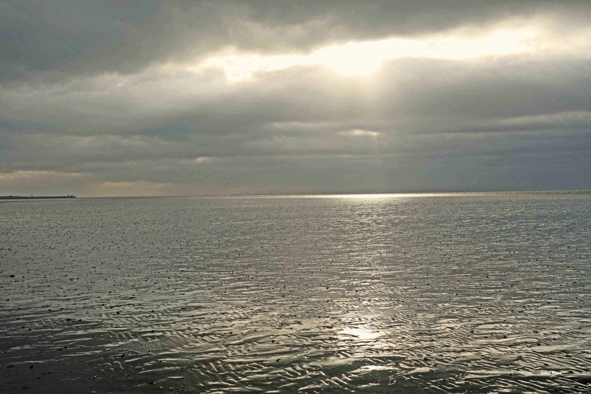 Sonnenstrahlen durchbrechen die Wolken und schimmern golden auf dem Wattboden