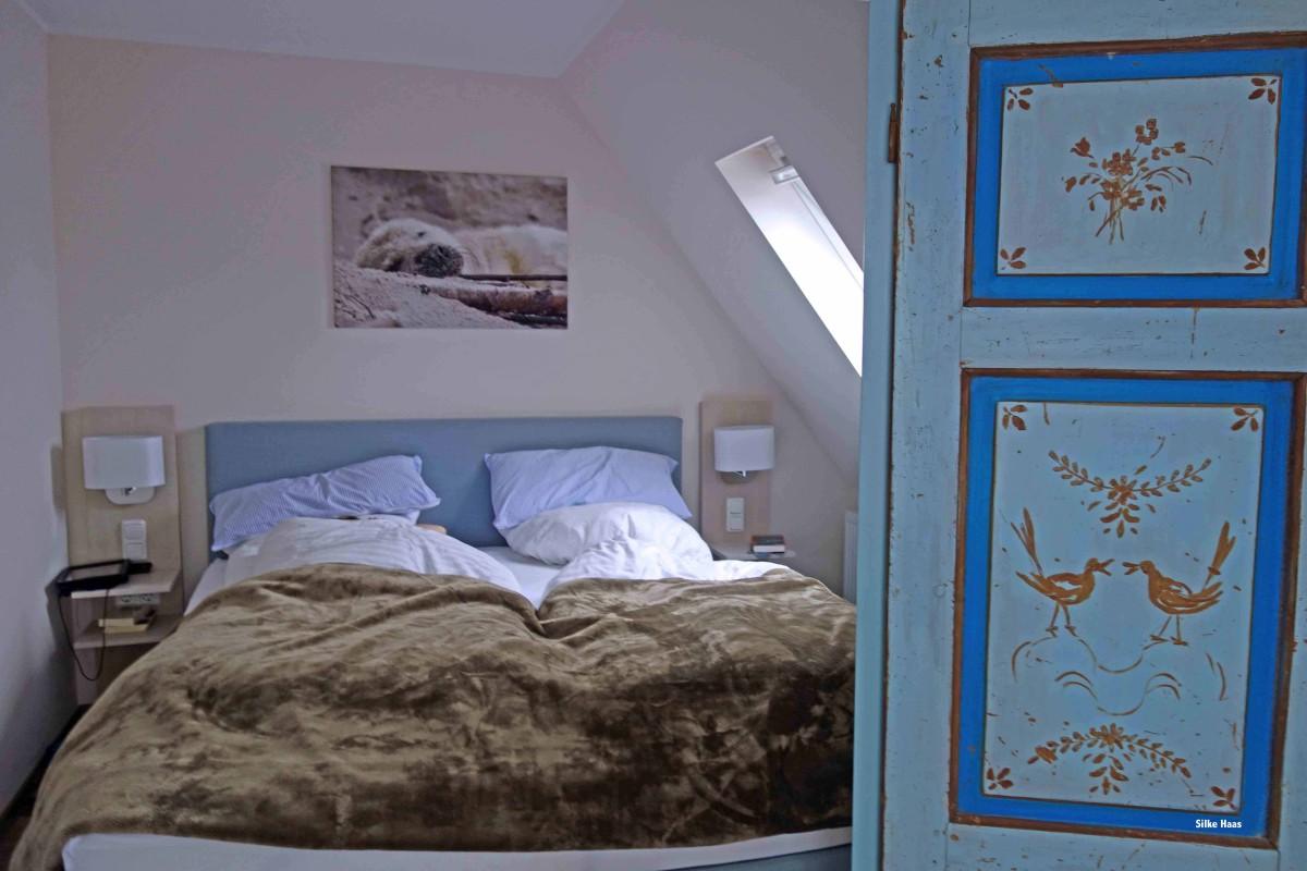 Das Bild einer schlafenden Robbe hängt über dem Bett und eine alte Alkoventür trennt das Schlafzimmer
