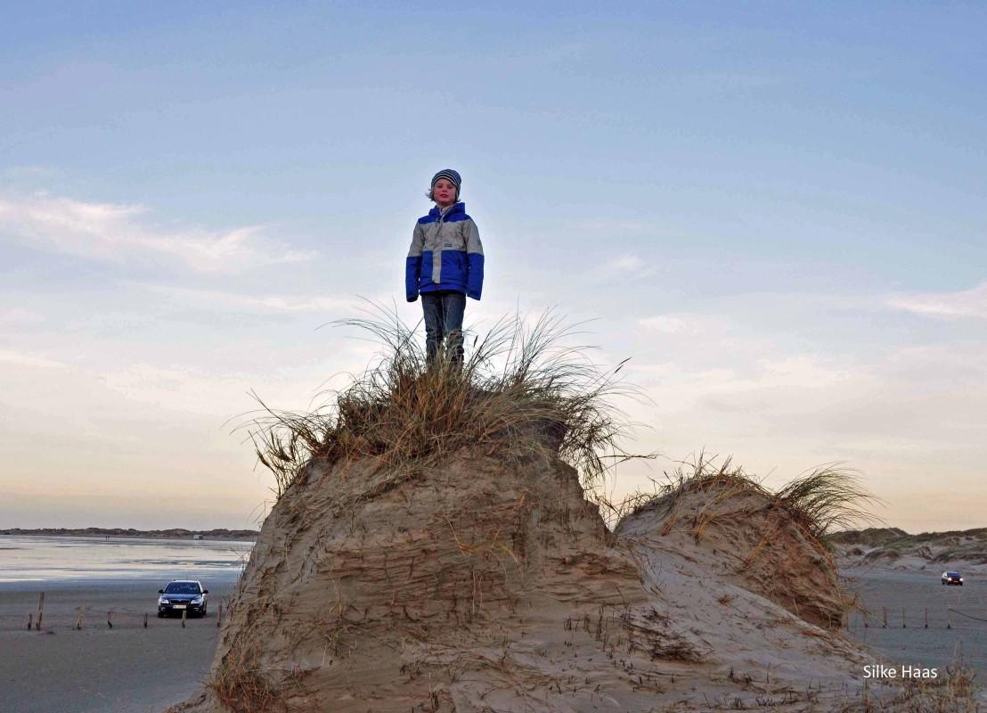 Kind steht auf einer Düne auf Römö und im Hintergrund stehen Autos im Watt