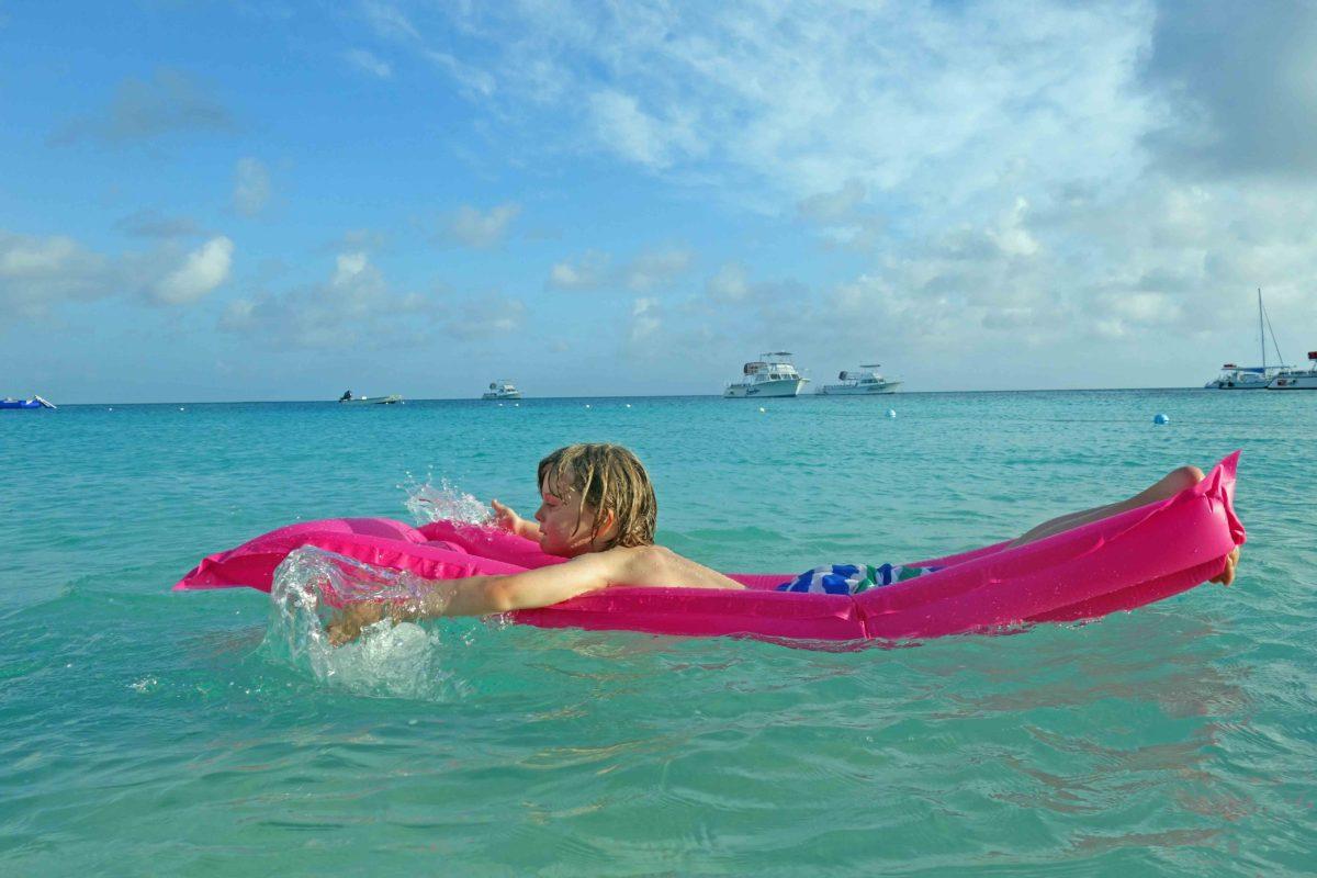 Frederik auf den Turks & Caicos paddelt auf einer pinken Luftmatratze im türkisblauen wasser