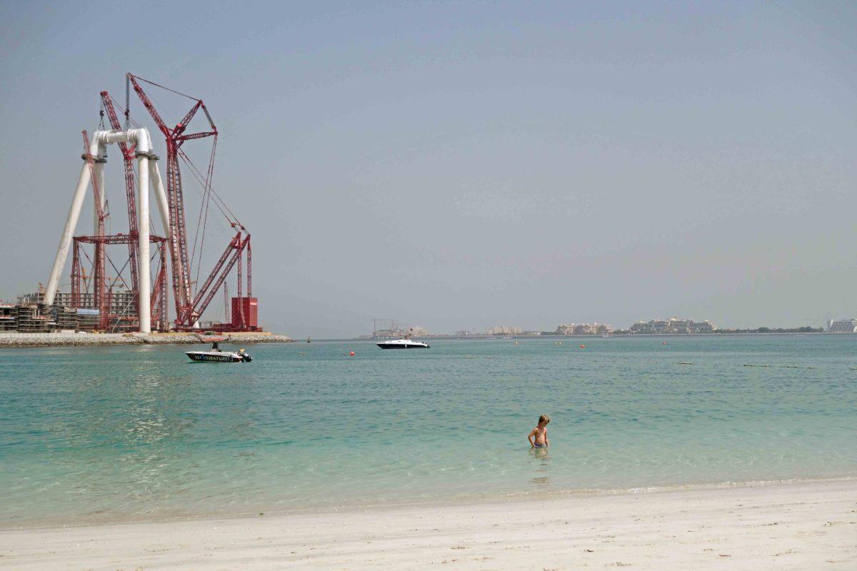 Kind badet in Dubai im Meer vor Baustelle Dubai Eye