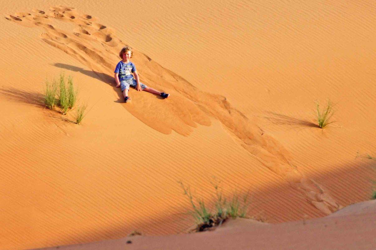 Kind schlittert auf dem Po eine Düne in Dubai herab