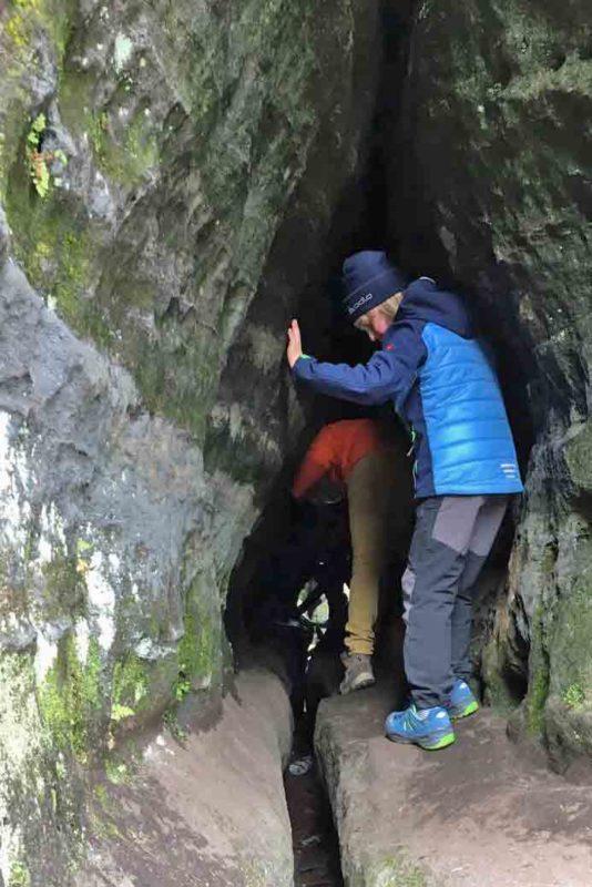 Kinder klettern durch einen schmalen Durchgang im Labyrinth im Elbsandsteingebirge