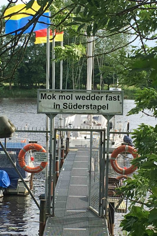 "Bootssteg in Süderstapel mit dem Schild ""Mok mol wedder fast in Süderstapel"""
